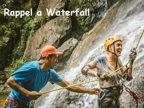 A guide helps a woman who has just rappelled down a waterfall in Belize. Belize Adventure Tours