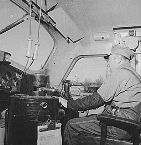 Engineer George Bertino in the cab of his diesel freight engine, ready to pull out of the Atchison, Topeka and Santa Fe Railroad yard at Winslow, Arizona in March 1943.