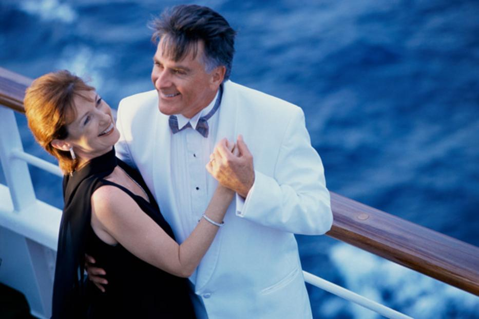 Newlywed couple in tuxedo and fancy gown dancing on a yacht