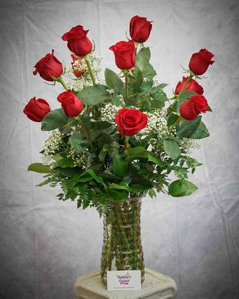 Beautiful vase arrangement designed with one dozen 70 cm red roses in a utility glass vase with filler flower and a variety of foliage.