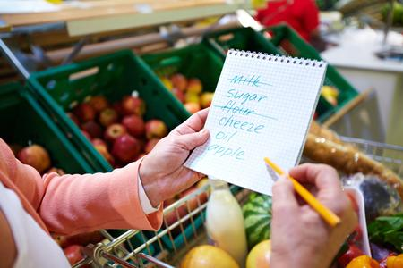 Woman's hands holding a grocery of six items, two of which have been crossed off, over a full grocery cart in the produce department