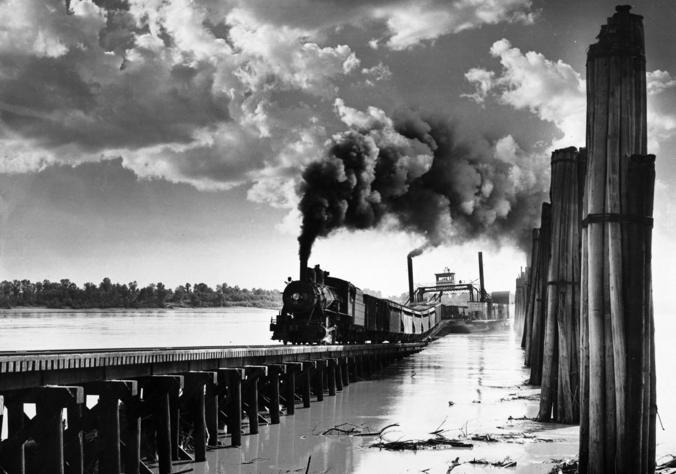 A Missouri-Illinois steam locomotive unloading railcars from a train ferry, circa 1955.