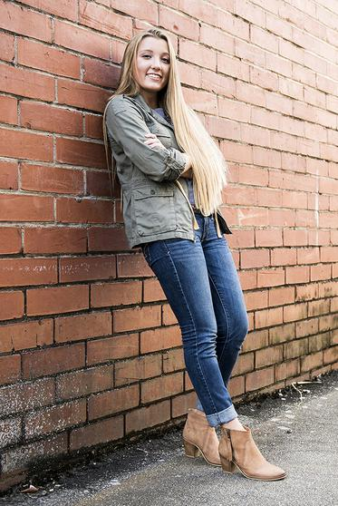 A picture of the model Ashlee leaning on a red brick wall.