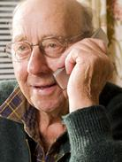 Image of older male adult wearing green sweater and glasses making a telephone call on his mobile device.