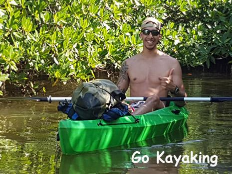 Young man sits on a kayak with a thumbs up clearly enjoying his time in Belize. Belize Adventure Tours