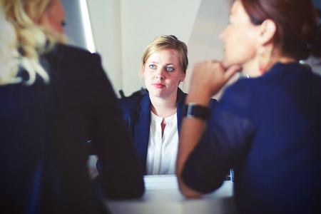Woman listening attentively as two women have a discussion