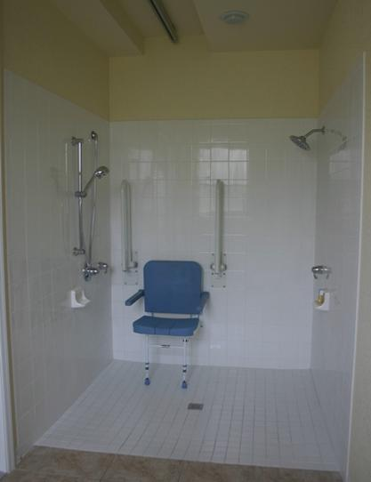 Level access shower with wall mounted shower seat and grab bars