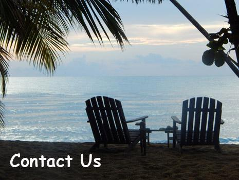 Two wooden beach chairs sit at the edge of the Caribbean Sea in Belize. All Inclusive Beach Vacations