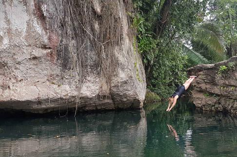 A woman dives from a large rock out cropping and into a pool in a river. Moses rock in Soldier Creek in Belize. All Inclusive Vacation Packages