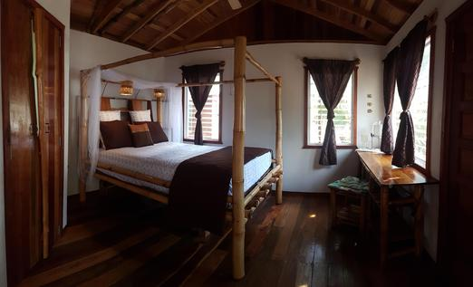 A bamboo bed with surround mosquito netting in the Bamboo Bungalow at Leaning Palm Resort in Belize.