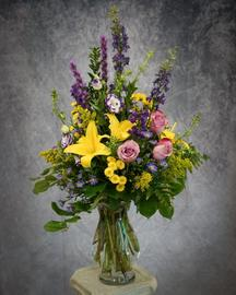 Lilies, larkspur, button mums, solidago and roses are just a few of the flowers you will find in this arrangement that mimics what you would see strolling through a field of wild flowers.