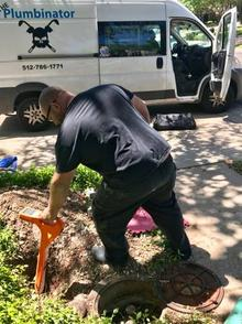The Master Plumber holds an orange leak location device, leaning over to lower it into a hole in the yard. The beeps will tell him if the leak is in that spot. The Plumbinator truck is in the background with the door open