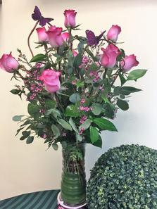 A dozen long stem color roses arranged in a clear glass vase,accented with a tropical leave swirl. Beautiful mixed foliage, filler, curly willow branch loops and a couple of butterflies to complete the design