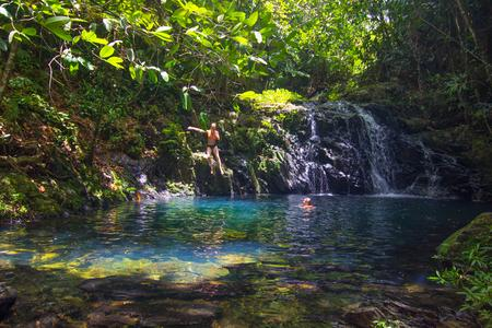 People swimming in a pool beneath a waterfall in Mayflower Bocawina Park in Belize. Belize Adventures