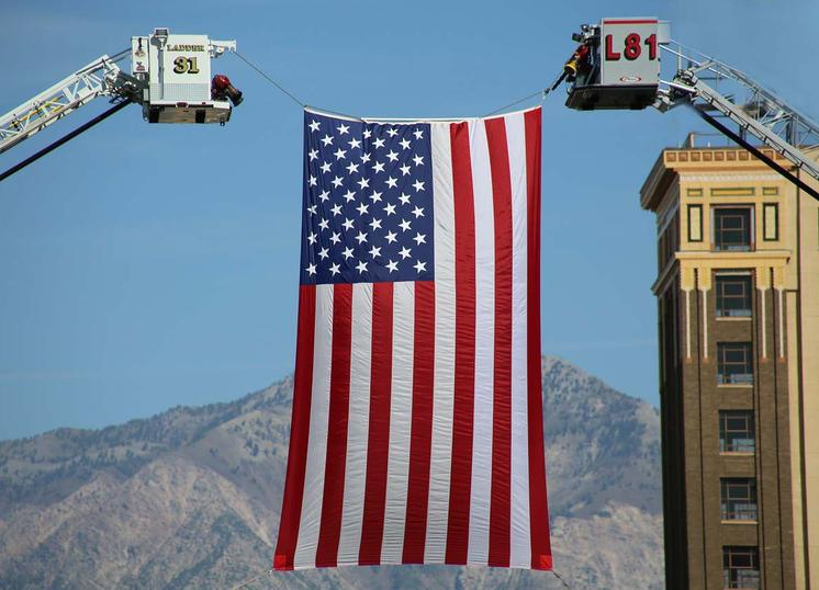 two fire department cranes lifting giant flag, building just behind it, mountains in distance