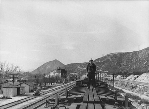 A Santa Fe Railroad brakeman atop a train that has paused at Cajon, California, to cool its brakes after descending Cajon Pass in March 1943. Jack Delano, Library of Congress.