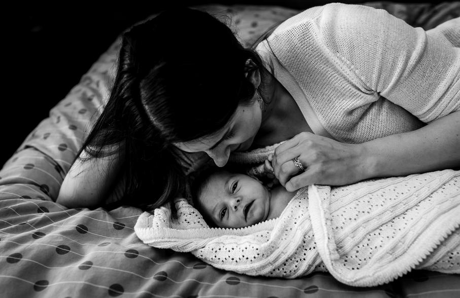 mother adoring her newborn baby during newborn family photography session