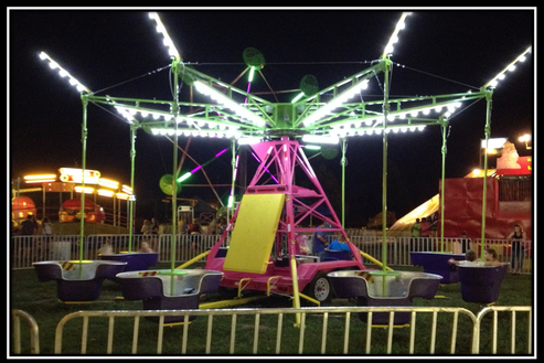Mind winder carnival ride for sale lit up at night