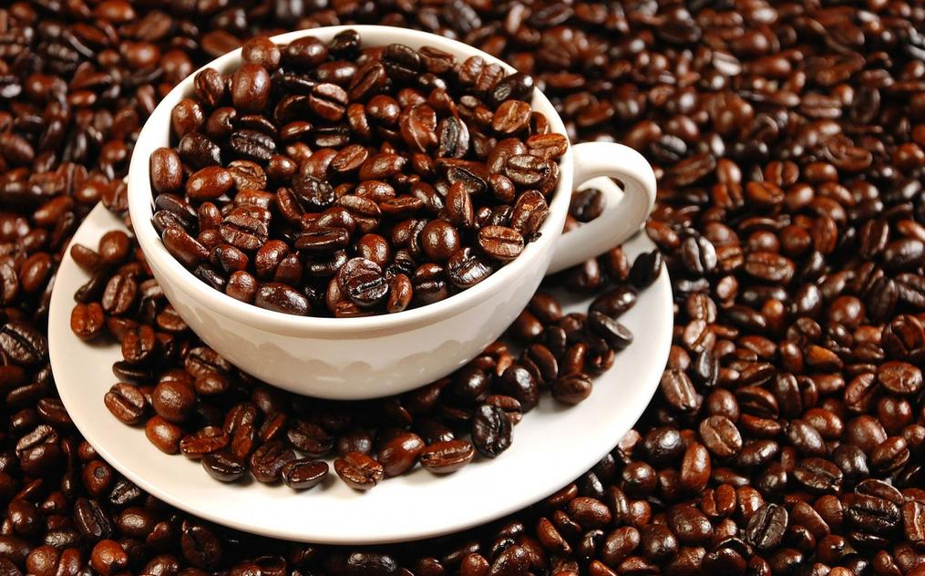 a huge picture of a coffee cup surrounded by coffee beans