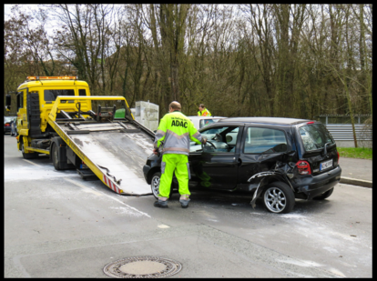 tow truck operator loading wrecked car