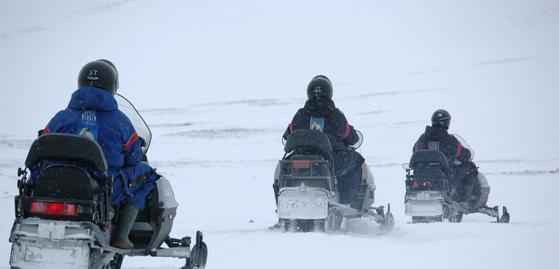 Facing the backs of three snowmobilers riding in a snowy field