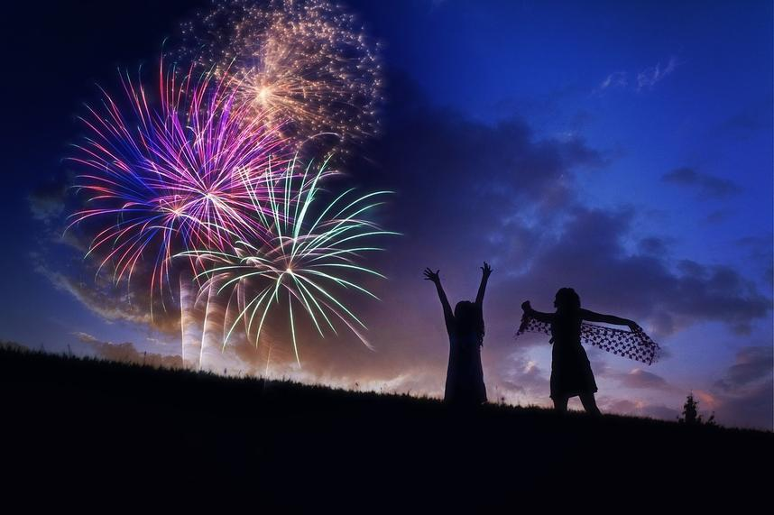 purple, gold, red and green fireworks above silhouetted hillside with two silhouetted girls dancing and raising their arms