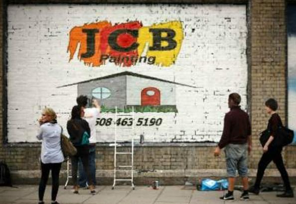 Jcb Painting logo painted on a brick wall.