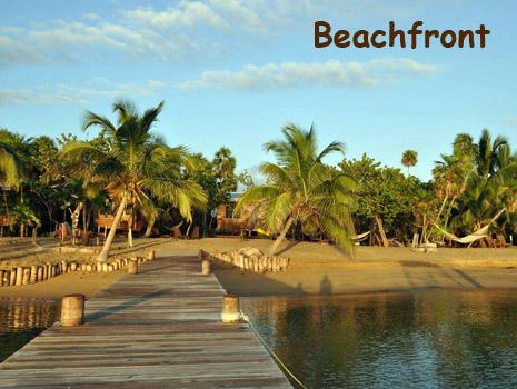 A wooden dock leads to the beach at Leaning Palm Resort in Belize. Beach Vacations in Belize!
