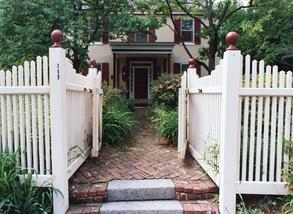 Umpleby House Bed & Breakfast Inn, front entrance, brick walkway, white picket fence, plants and trees.