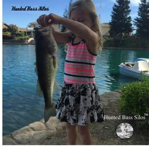 Small girl holding a bass caught with a Hunted Bass Silos lure