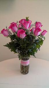 Glass Vase designed with a dozen beautiful pink long stem roses, complimented with a mix of foliage and filler flower.