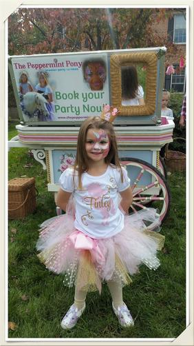 little girl wearing unicorn face paint in front of flower painted flower cart