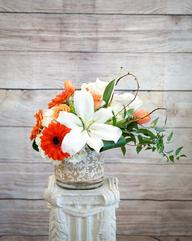 Fragrant white oriental lilies with bright orange gerber daisies accented with peach roses.