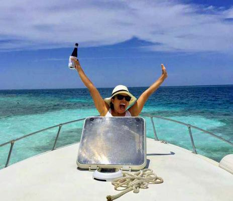 A very happy woman pops out of the hatch on a boat in the Caribbean Sea. She is holding a Belikin beer. Belize Adventure Tours