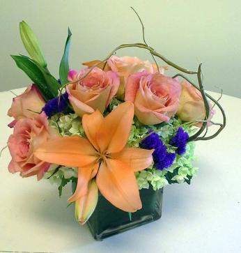 Square vase arrangement designed with green hydrangea, orange lilies, pink roses, purple statice, curly willow, and a variety of foliages.