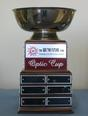 Picture of Optic Cup trophy - silver, round cup sitting on top of wooden base which displays engraved names of each winning foursome since 1997