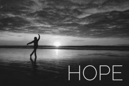 "A picture of a person on a beach, sunrise with the word ""HOPE"" overlayed"