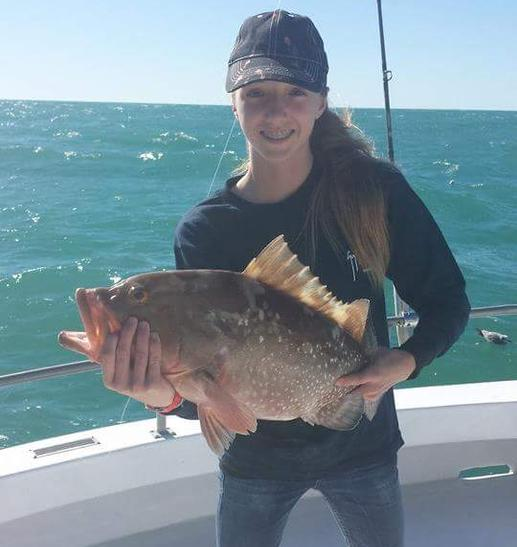 A girl enjoying our fishing charter in Fort Myers Beach, FL