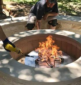 A plumber lights a new gas outdoor fire pit, flames erupt from a star shaped gas burner in the middle of a stone pit