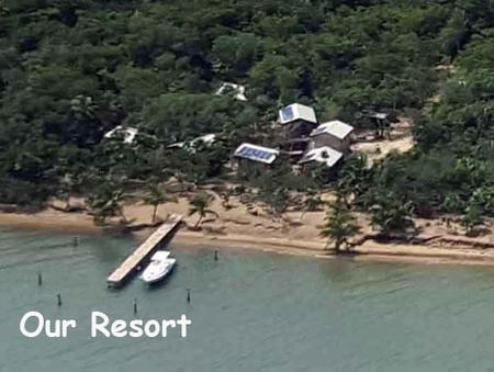 An aerial photo of Leaning Palm Resort with boat along side the dock. Leaning Palm Resort features 3 bungalows and a restaurant and bar for your beach vacation in Belize.