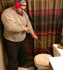 Photo of the master plumber wearing headphones and using specialized leak listening equipment that looks like a metal rod to listen to a toilet for leaks