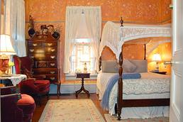 Special Amenity Rooms & Suites - Image of the Canopy Room in the Wedgwood Inn. Stenciled walls, lace canopy on bed, Victorian chairs, antique furniture.