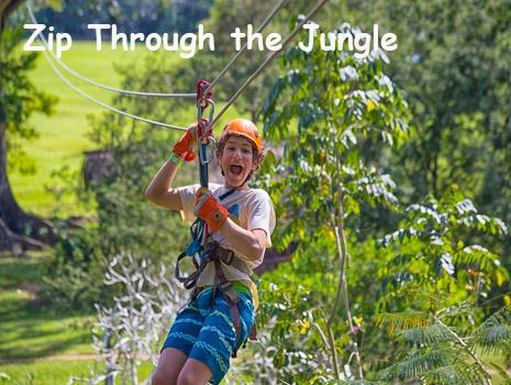A young boy smiles as he makes his way along a zip line in the Belize rain forest. Belize Adventure Tours