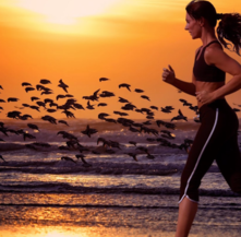 Women running along water with birds in background in sunlight