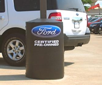 Light pole base covers with graphic logos identify dealership inventory areas.