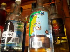 Local spirits of rum, gin and banana liquor rest on the bar shelves ready to mix up a Caribbean Cocktail. Belize Vacations