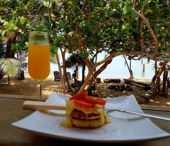 A mimosa and a plate of eggs benedict rest on the bar rail with a view of the Caribbean Sea. Beach Side Restaurants in Belize
