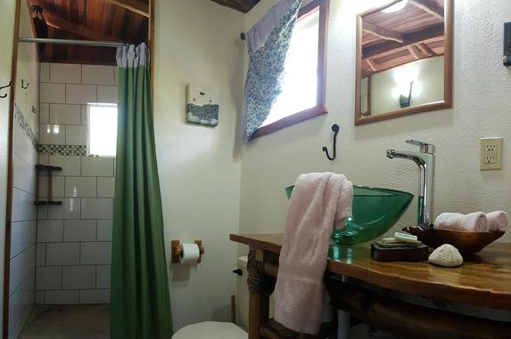 Greens and purples decorate the bathroom in the Bamboo Bungalow at Leaning Palm Resort in Belize.