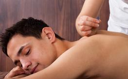 Male, eyes closed, brown, acupuncture needles being inserted by acupuncturist in his back as he lays on his right cheek, face down
