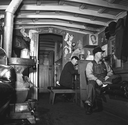 A freight train conductor (seated at desk) on the Chicago and Northwestern Railroad.